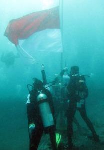 PENGIBARAN BENDERA  - Dua petugas mengerek Bendera Merah Putih di dalam laut, saat mencatat rekor upacara bendera dalam laut pertama kali di seluruh dunia yang diikuti 2.468 penyelam, di Pantai Malalayang Dua, Manado, Senin (17/8/2009) (foto:Danny Permana)