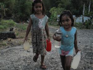 Anak-anak transmigran Serei melintasi jalan aspal yang sudah tak ada aspalnya lagi.