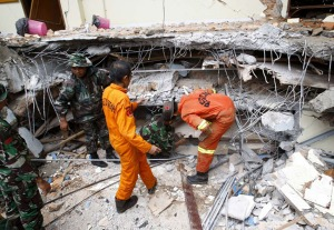 Petugas SAR dan TNI mencari korban dari balik reruntuhan