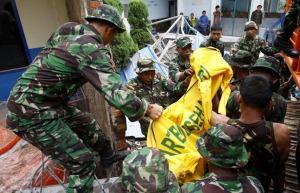 Personel TNI mengevakuasi jenazah dari reruntuhan bangunan yang ambruk akibat gempa bumi 7,6 skala Richter di Padang, Sumatera Barat.