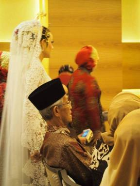 Pengantin perempuan berjalan di samping HM Sani yang sedang duduk menghadiri acara pernikahan di Singapura, Selasa (29/12/2015) siang. (Foto: istimewa)