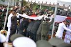 Para petugas membentangkan Bendera Merah Putih di atas liang lahat saat prosesi penguburan jenazah Gubernur Kepri Drs HM Sani di Taman Makam Pahlawan KM 5 Tanjungpinang, Sabtu (9/4/2016). Foto: eddy mesakh