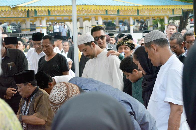 Keluarga dan kerabat Almarhum HM Sani berdiri di sisi liang lahat saat prosesi pemakaman di Taman Makam Pahlawan KM5, Tanjungpinang, Sabtu (9/4/2016). Foto: eddy mesakh.