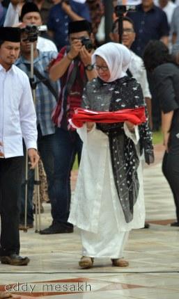 Hj Aisyah Muhammad Sani, istri almarhum Drs HM Sani membawa bendera yang diterimanya dari Menteri Dalam Negeri Tjahjo Kumolo, saat upacara pemakaman di Taman Makam Pahlawan, Tanjungpinang, Sabtu (9/4/2016). Foto: eddy mesakh.