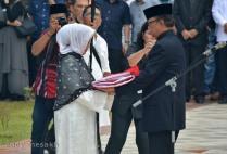 Mendagri Tjahjo Kumolo menyerahkan Bendera Merah Putih kepada Ny Hj Aisyah Muhammad Sani, istri almarhum Gubernur Kepri Drs HM Sani, saat upacara pemakaman di Taman Makam Pahlawan Batu 5, Kota Tanjungpinang, Sabtu (9/4/2016). Foto: eddy mesakh